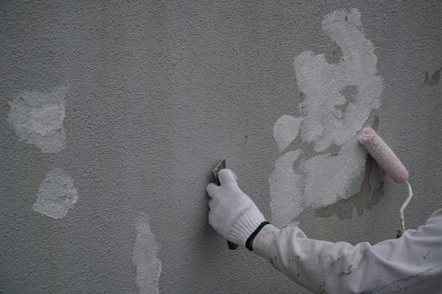 外壁にシーラーを塗装している人