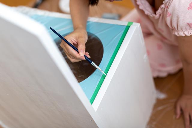 子どもが塗装をしている